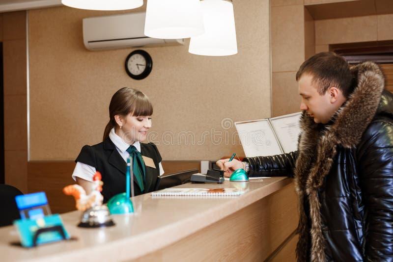 Convidado masculino na recepção do hotel durante o registro imagem de stock royalty free
