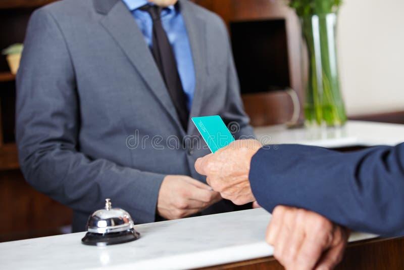 Convidado que dá o cartão chave ao recepcionista do hotel imagem de stock