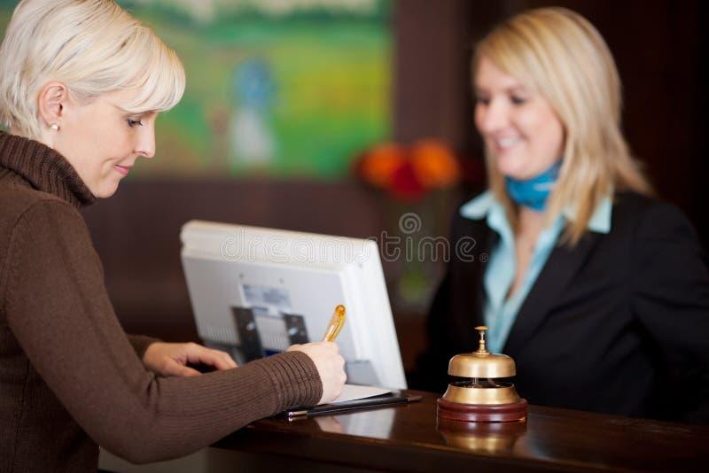 Convidado que enche-se acima de um formular no contador do hotel foto de stock royalty free