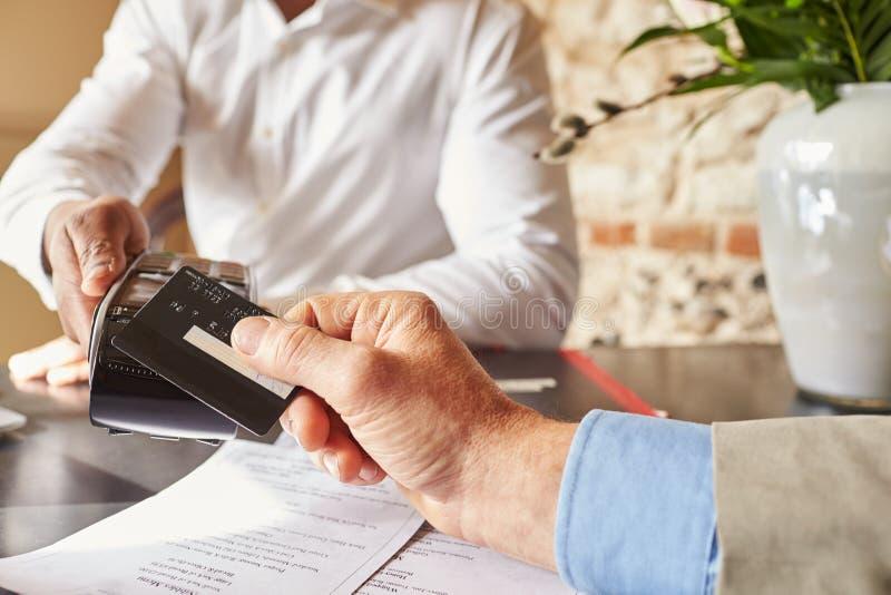 Convidado que faz o pagamento sem contato do cartão no hotel, detalhe das mãos fotografia de stock royalty free