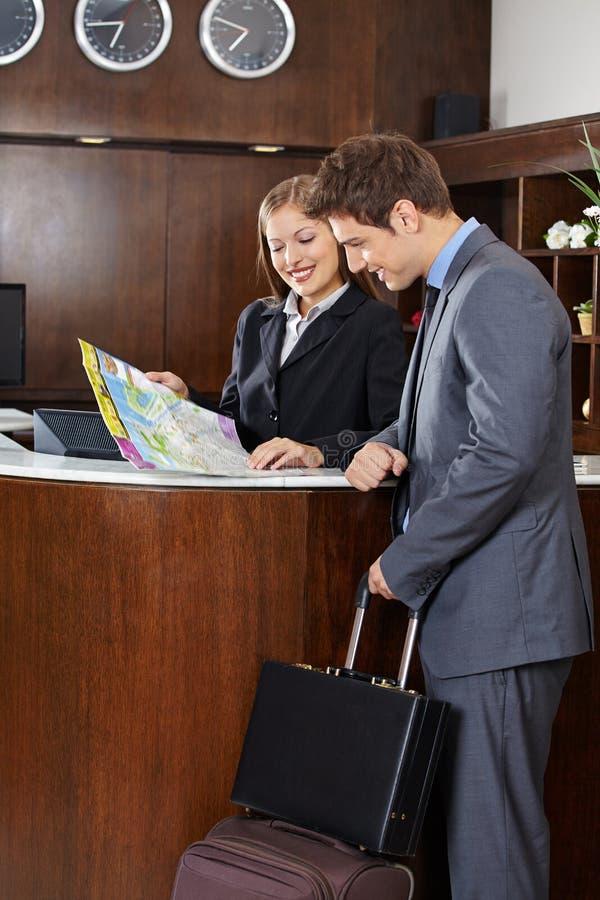 Convidado que olha o mapa da cidade com recepcionista do hotel foto de stock royalty free