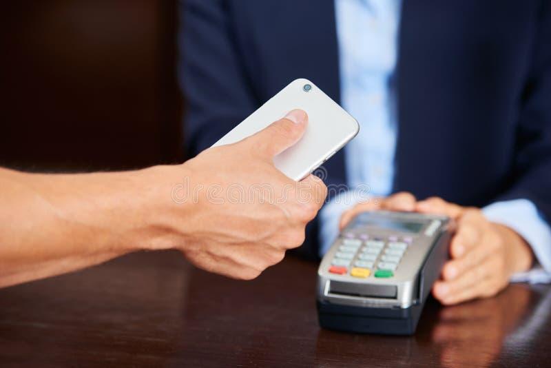 Convidado que paga com o smartphone na recepção do hotel imagem de stock royalty free