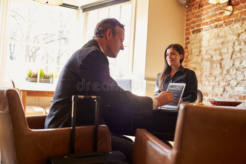 Convidado que verifica dentro na recepção do hotel que usa o tablet pc foto de stock