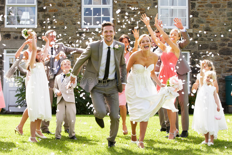 Convidados que jogam confetes sobre noivos fotografia de stock