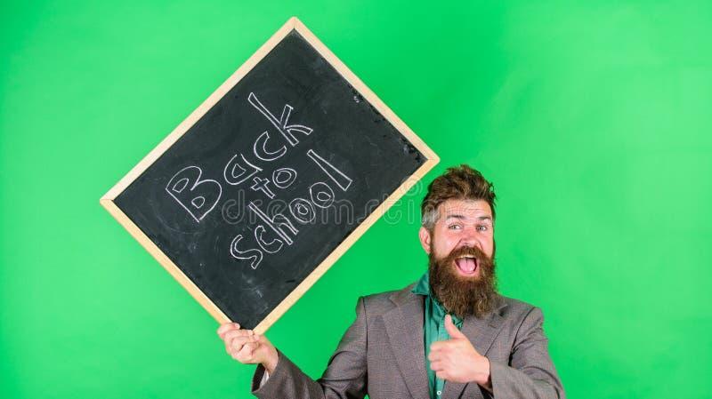 Convide para comemorar o dia do conhecimento O homem farpado do professor guarda o quadro-negro com inscrição de volta ao verde d fotos de stock