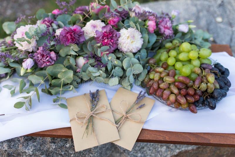 Convites do casamento nos envelopes do ofício com alguns ramos da alfazema perto da composição da flor e de uma bandeja com uva imagens de stock royalty free