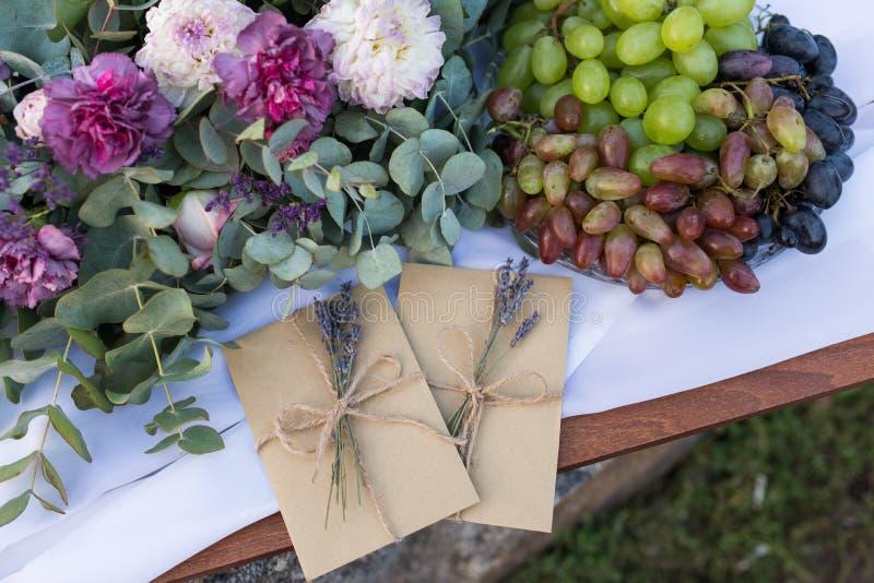 Convites do casamento nos envelopes do ofício com alguns ramos da alfazema perto da composição da flor e de uma bandeja com uva W imagem de stock