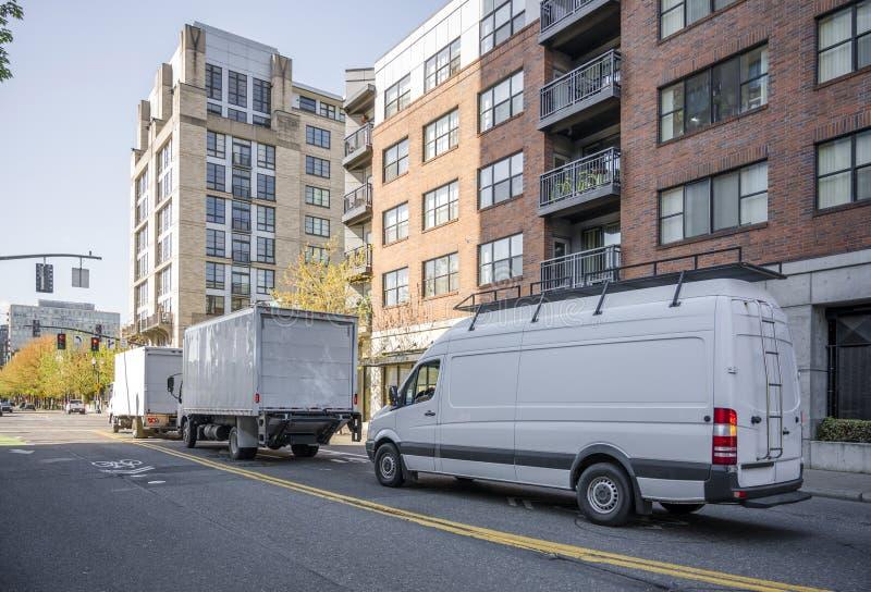 Convoy de diversos camiones con los remolques de la caja y la mini furgoneta compacta larga imagen de archivo