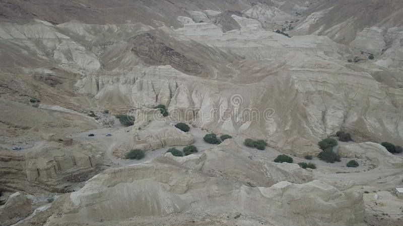 Convoy of SUV at desert mountains moving to the top through anciet caves stock photo
