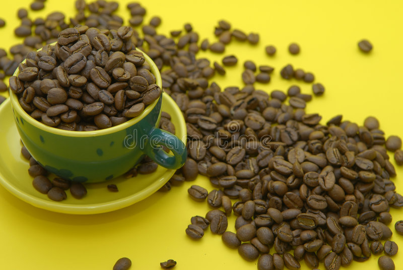Cooffee beans and cup. Coffee beans and cup on yellow background stock photography
