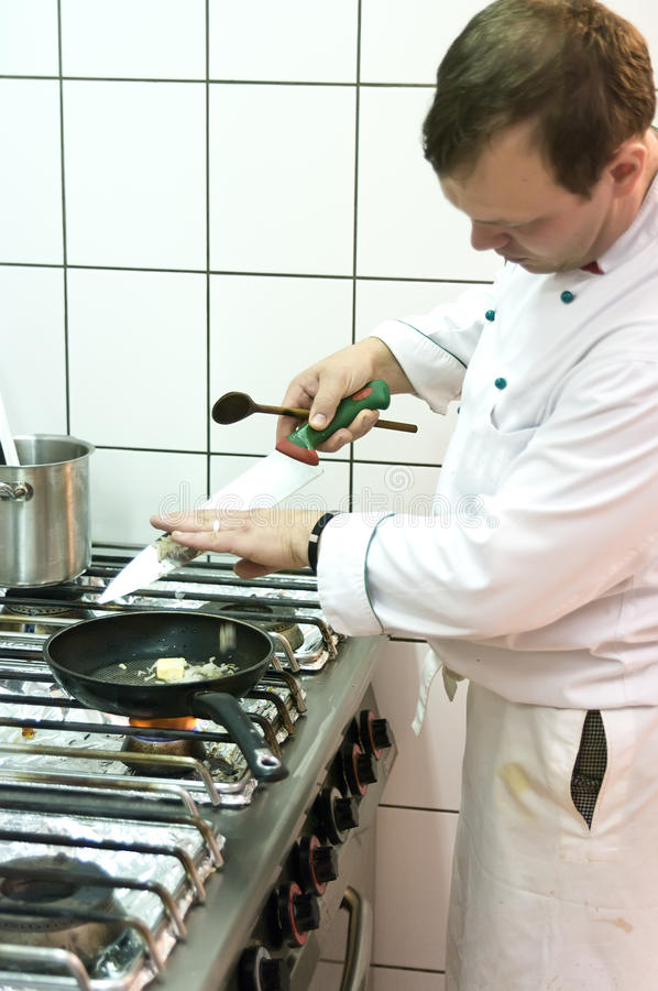 Cook. A cook working in commercial kitchen royalty free stock photography