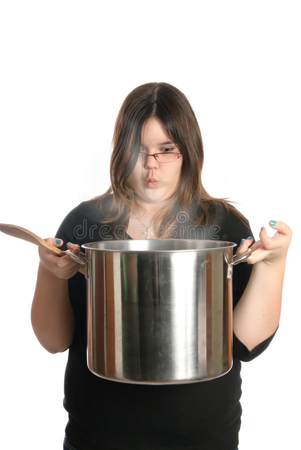Cook. A young girl is holding a large pot of steaming soup, isolated against a white background royalty free stock photo