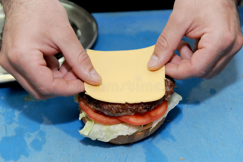 Cook adding cheese on burger. Preparing and making hamburger. Cook adding cheese on burger. Preparing and making hamburger in the kitchen royalty free stock images