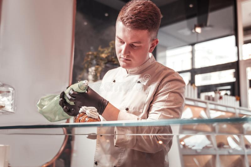 Cook adding cream to a fresh croissant royalty free stock photos
