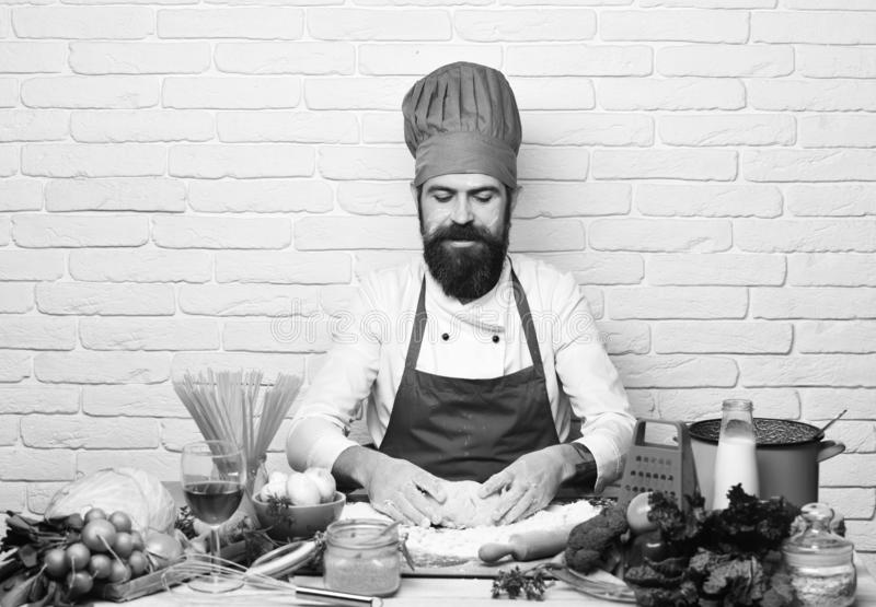 Cook with attentive face in burgundy uniform sits by table. With vegetables and kitchenware. Chef makes dough. Man with beard kneads dough on white brick wall stock image
