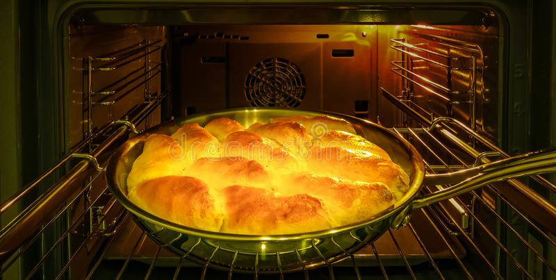 The cook bakes pies with apples for the holiday in the oven. stock photos
