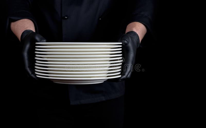 Cook in black uniform holds in his hands a stack of round white empty plates royalty free stock photo