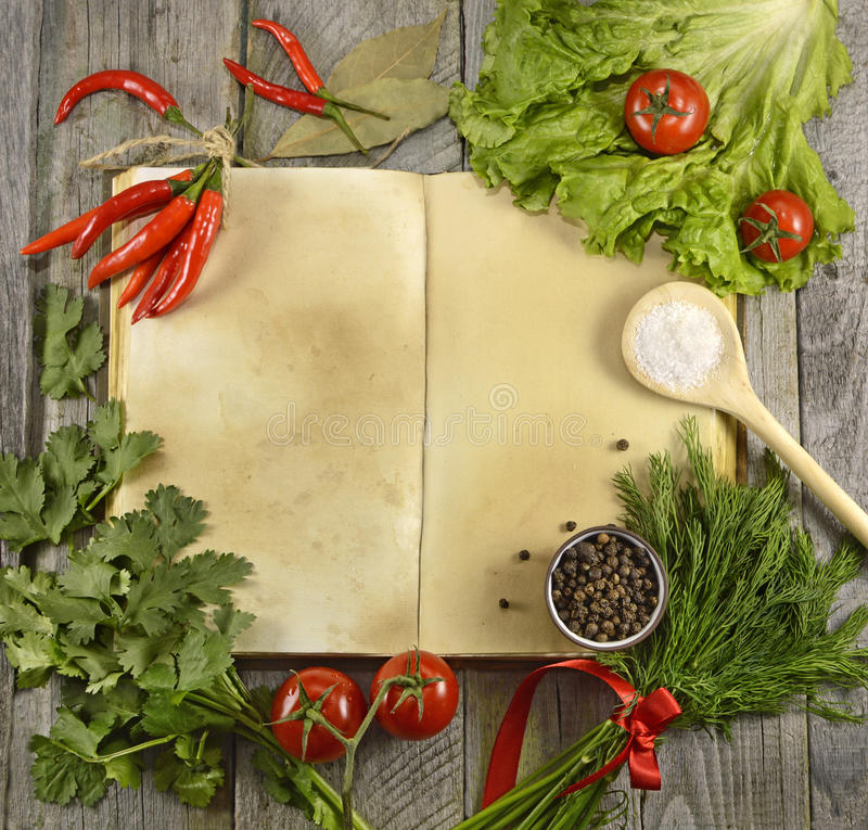 Cook book with vegetables and spices. Open cook book with vegetables and spices on wooden table stock photography