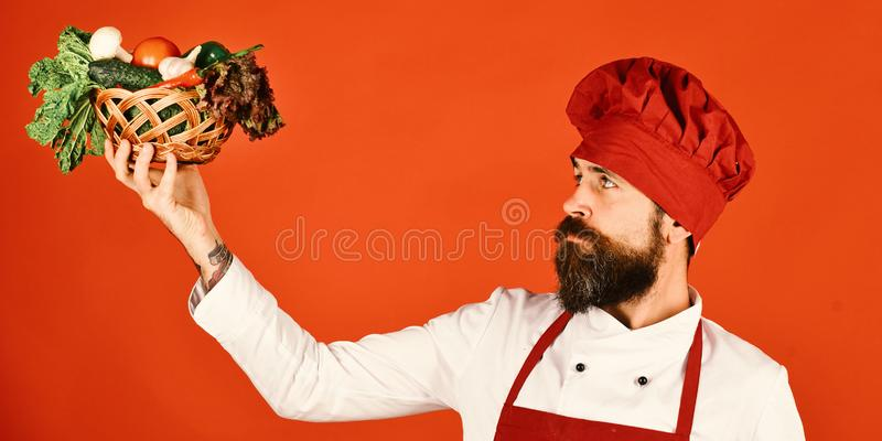 Cook with calm face in burgundy uniform looks at vegetables. In wicker bowl. Man with beard on red background. Vegetarian restaurant concept. Chef holds lettuce stock photography
