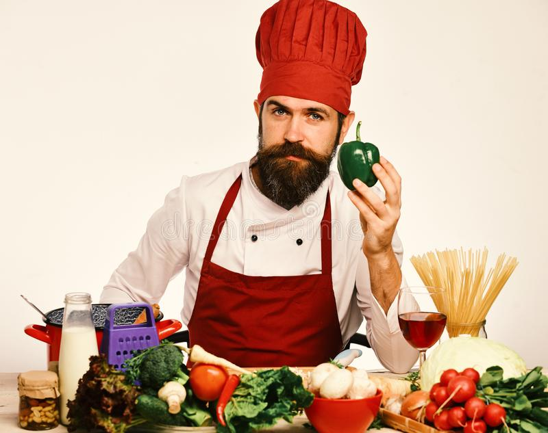 Cook with calm face in uniform sits by kitchen table. Cook with calm face in burgundy uniform sits by kitchen table with vegetables and kitchenware. Professional stock photography
