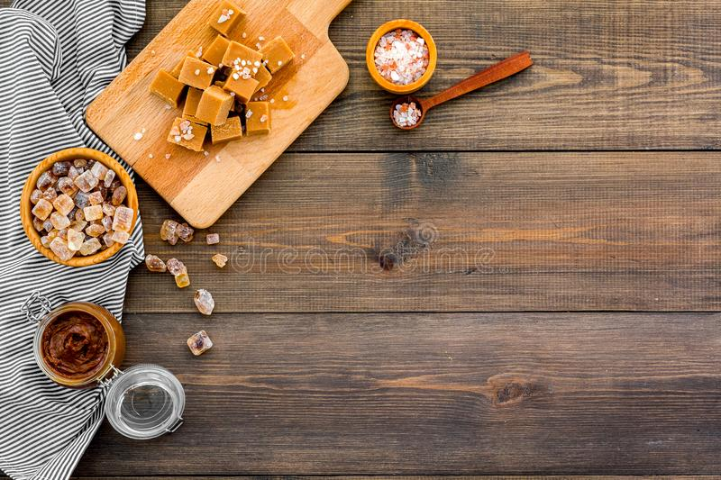 Cook caramel sauce. Melted caramel in glass jar, caramel cubes on cutting board, sugar and salt on dark wooden. Background top view royalty free stock images