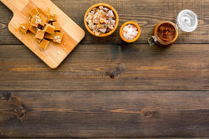 Cook caramel sauce. Melted caramel in glass jar, caramel cubes on cutting board, sugar and salt on dark wooden. Background top view stock image