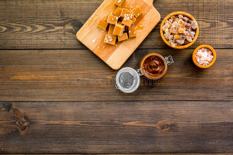 Cook caramel sauce. Melted caramel in glass jar, caramel cubes on cutting board, sugar and salt on dark wooden. Background top view royalty free stock photography