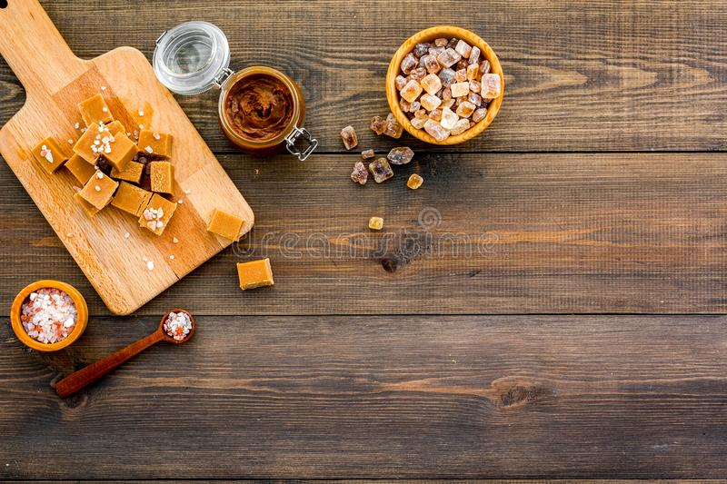 Cook caramel sauce. Melted caramel in glass jar, caramel cubes on cutting board, sugar and salt on dark wooden. Background top view royalty free stock image