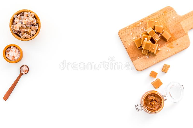 Cook caramel sauce. Melted caramel in glass jar, caramel cubes on cutting board, sugar and salt on white background top stock photo