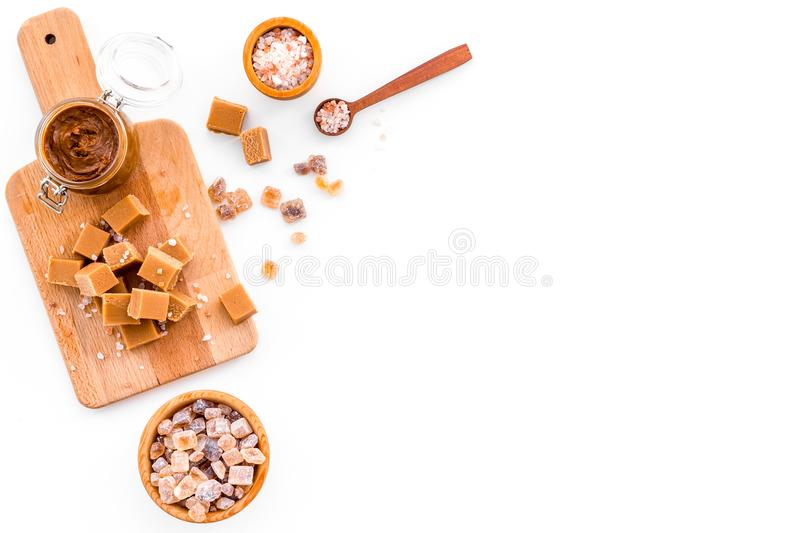 Cook caramel sauce. Melted caramel in glass jar, caramel cubes on cutting board, sugar and salt on white background top. View stock image