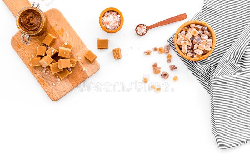 Cook caramel sauce. Melted caramel in glass jar, caramel cubes on cutting board, sugar and salt on white background top. View royalty free stock photography