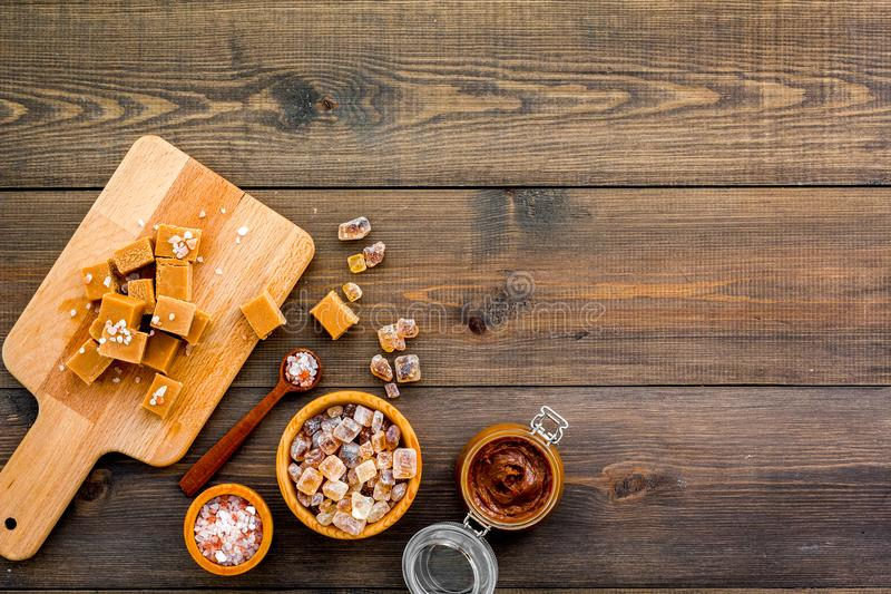 Cook caramel sauce. Melted caramel in glass jar, caramel cubes on cutting board, sugar and salt on dark wooden. Background top view stock photo