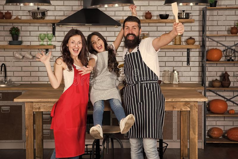 Cook it with care. Cook team while happy working. Little girl with parents in apron. Family day. Happy family in kitchen royalty free stock photo