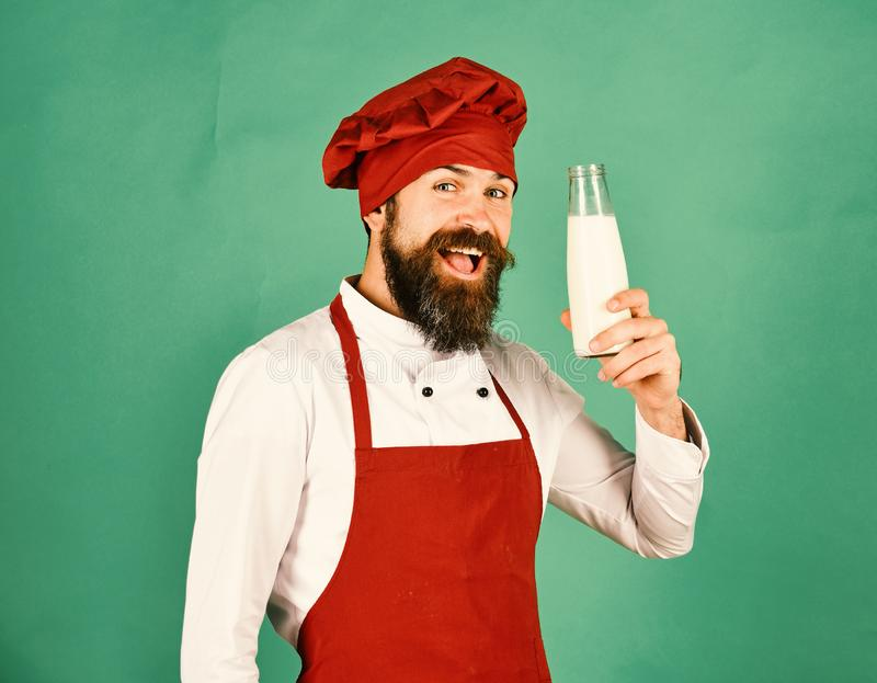 Cook with cheerful face in burgundy uniform holds milk. stock photography