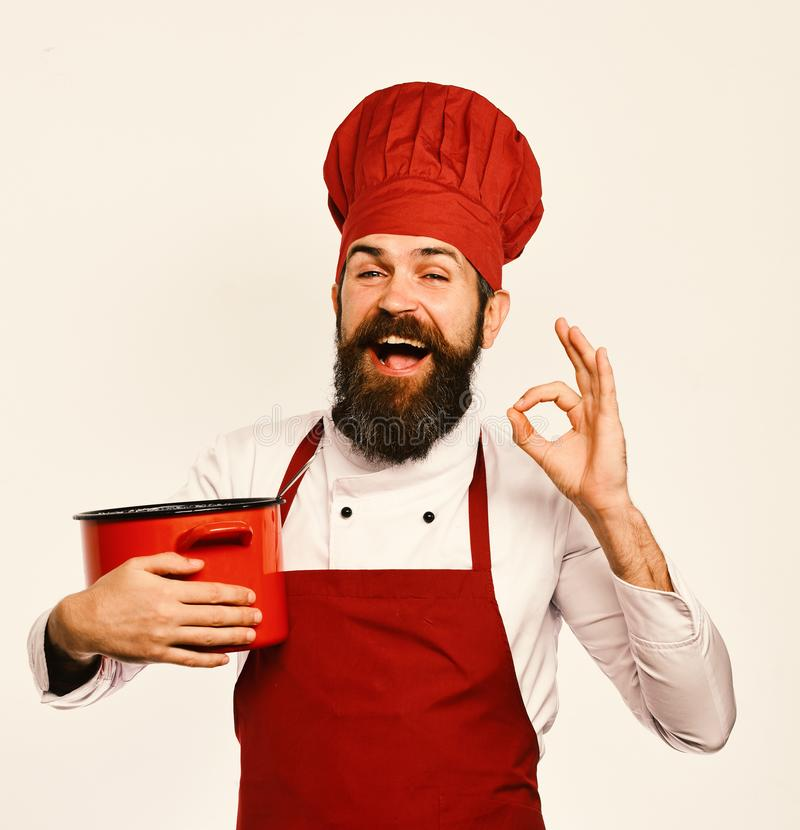 Cook with cheerful face in burgundy uniform has casserole royalty free stock images