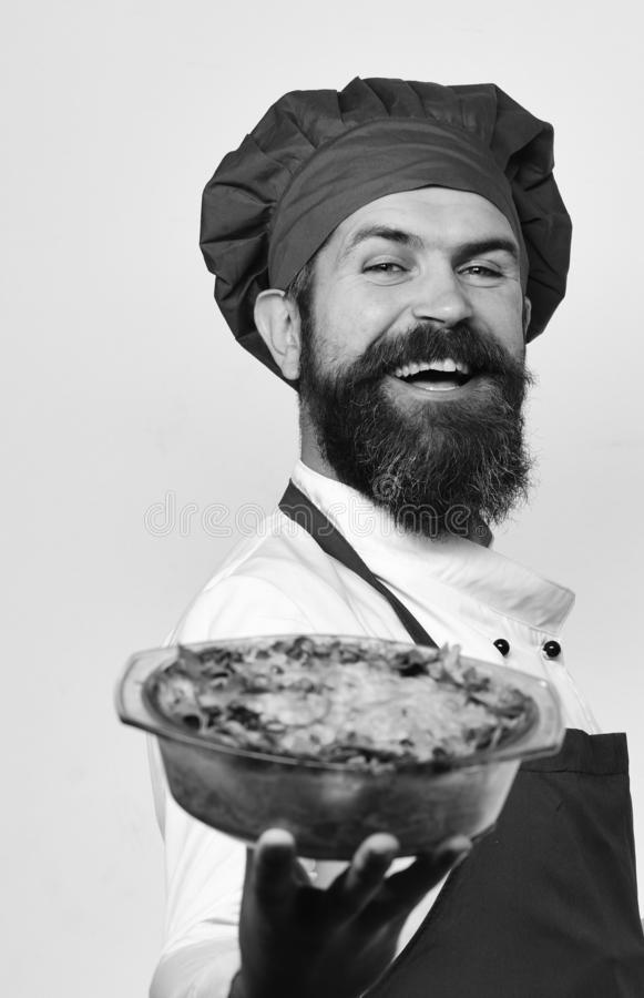 Cook with cheerful face in burgundy uniform holds baked dish stock images