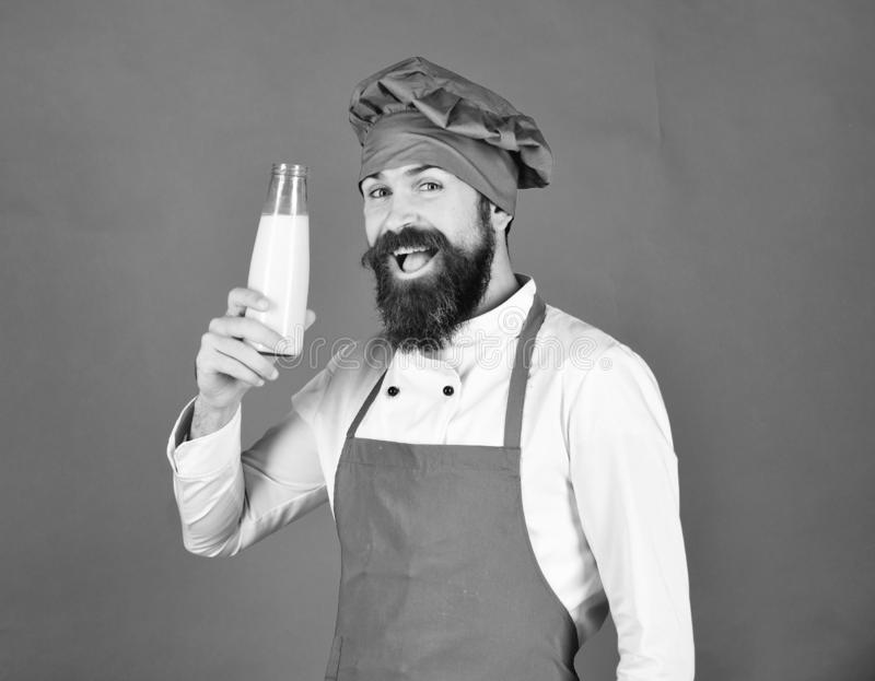 Cook with cheerful face in burgundy uniform holds milk. stock photos