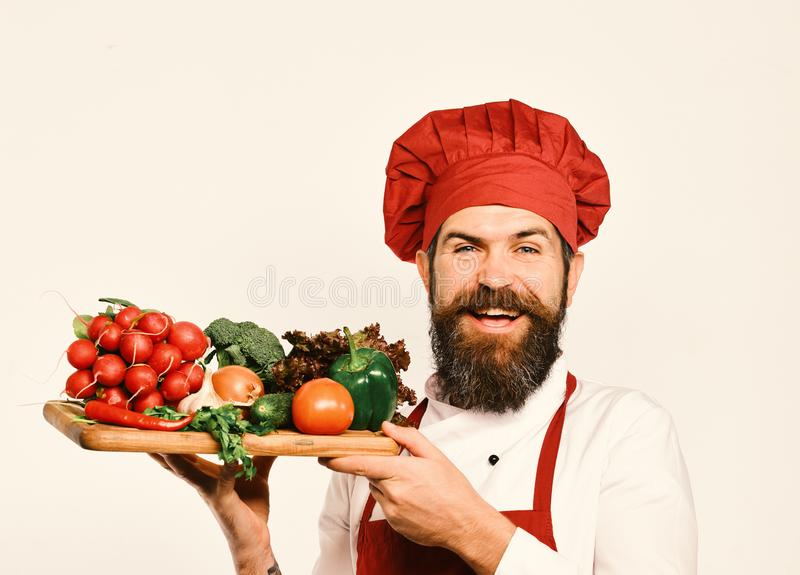Cook with cheerful face in burgundy uniform holds salad ingredients. Chef holds board with fresh vegetables. Cooking and royalty free stock photography