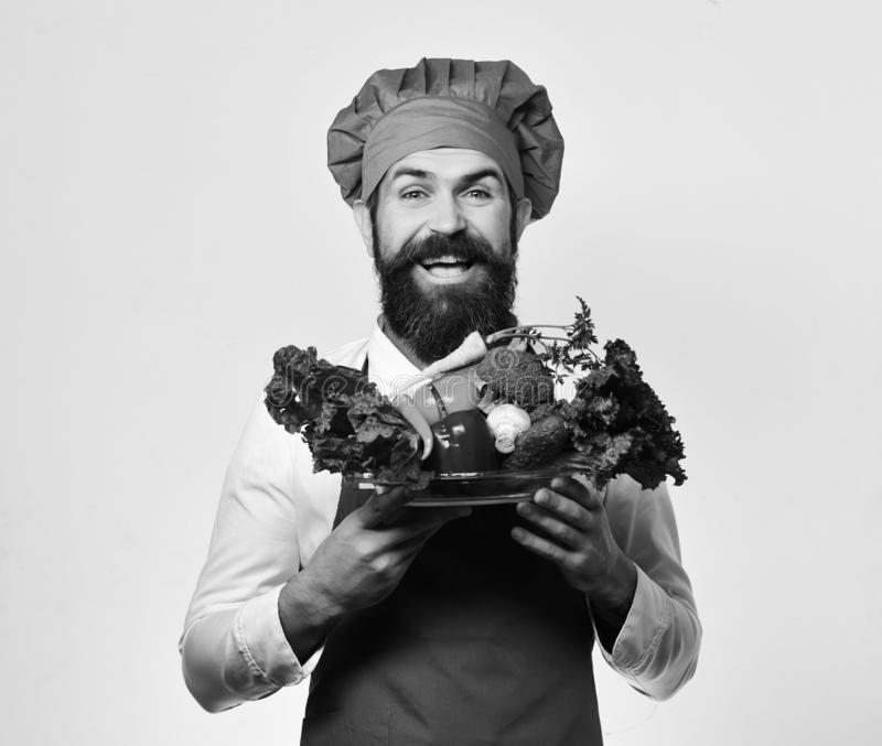 Cook with cheerful face in burgundy uniform holds salad ingredients royalty free stock images