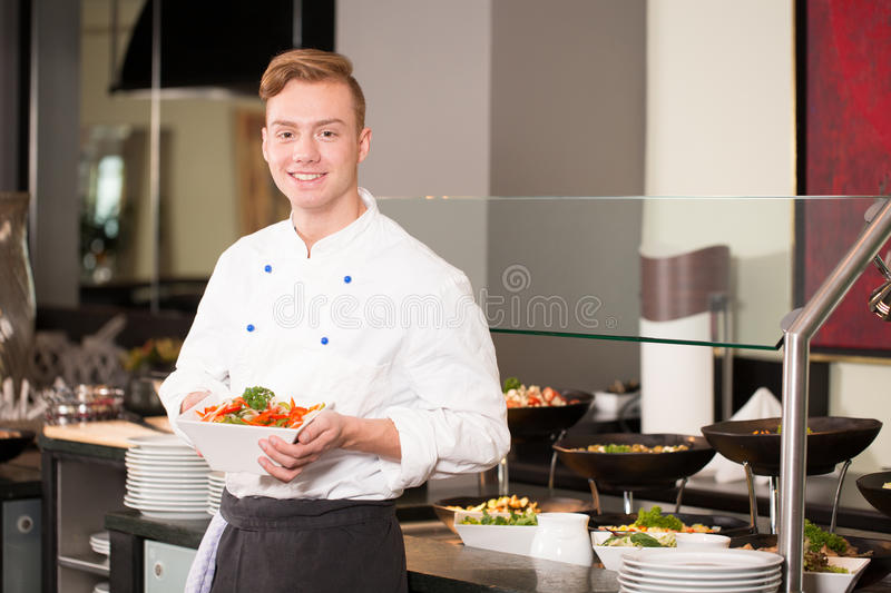 Cook or chef from catering service posing with food at buffet. Cook or chef from catering service posing with food in front of buffet stock image