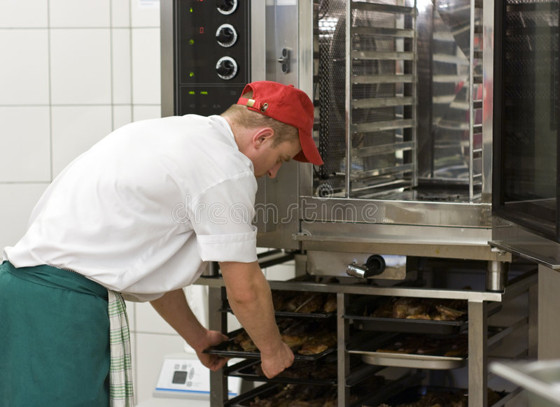 Cook at commercial stove. A professional stove (oven) used in a commercial kitchen for preparing large amounts of food. The cook operating the machine stock image