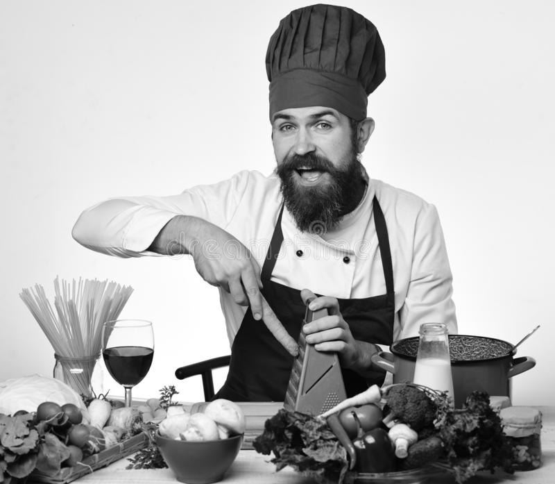 Cook with curious face sits by kitchen table with vegetables. Kitchenware and wine. Chef prepares meal. Man with beard grates carrot on grater on white stock image