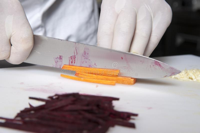 The cook cuts carrots into slices in the restaurant kitchen. On a plastic board stock photo