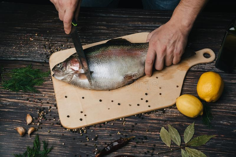 Cook cuts fresh fish in the kitchen. Raw trout for cooking stock photo
