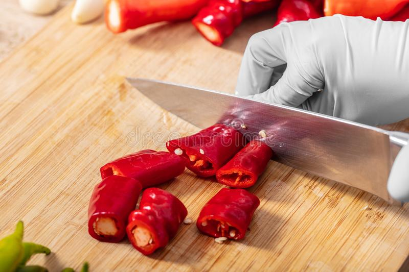 Cook cutting hot chili peppers royalty free stock image