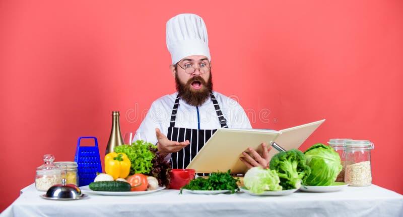 Cook czyta ksi??kowych przepisy r pr?ba co? nowy Cookery na m?j umysle Kulinarna umiej?tno?? Ksi??kowi przepisy according zdjęcia stock