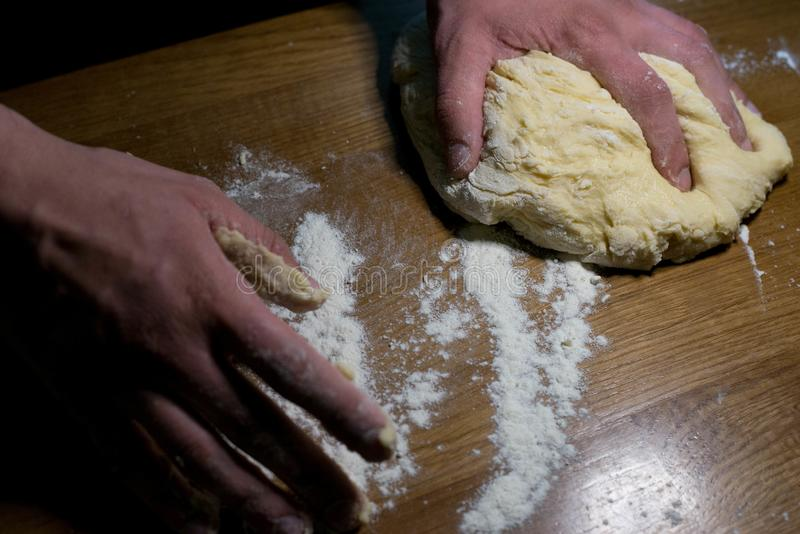 The cook from the dough begins to make baking dishes. The cook kneads the dough before rolling it out on a wooden table royalty free stock photography