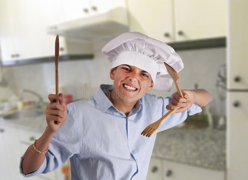 Cook fighting with spoons. Young chef with attitude fighting with kitchen tools royalty free stock image