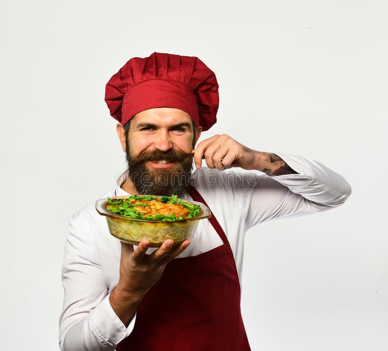 Cook with flirty face in burgundy uniform holds baked dish. Curling mustache. Man with beard on white background. Cooking and vegetarian diet concept. Chef stock photography