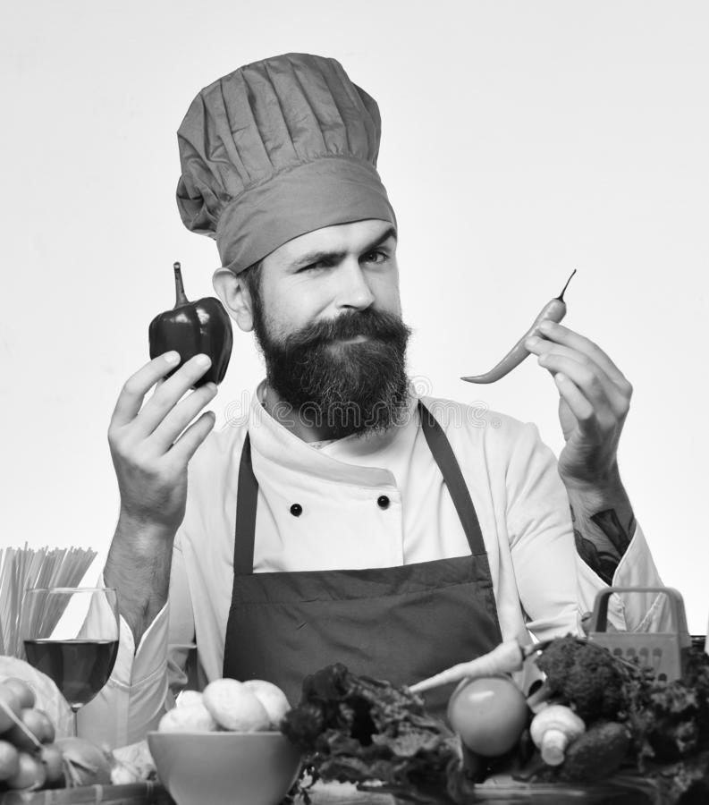 Cook with flirty face in uniform sits by kitchen table. With vegetables and kitchenware. Chef prepares meal. Professional cookery concept. Man with beard holds royalty free stock photos